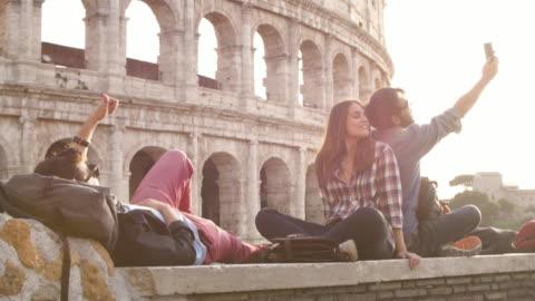 selfies sırt çantaları ile smartphone ile güneş gözlüğü mutlu güzel kız uzun saç ağır çekim alarak günbatımında roma colosseum önünde oturan üç genç arkadaşlar turist - seyahat destinasyonları stok videoları ve detay görüntü çekimi