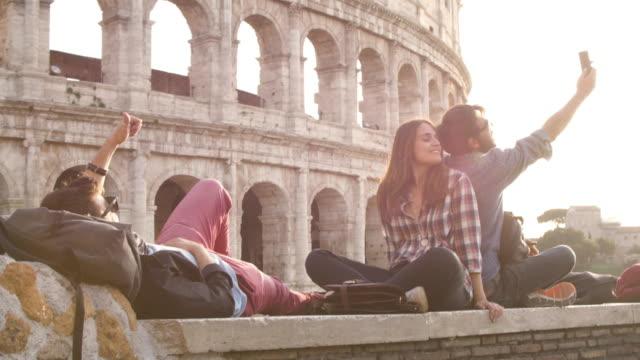 selfies sırt çantaları ile smartphone ile güneş gözlüğü mutlu güzel kız uzun saç ağır çekim alarak günbatımında roma colosseum önünde oturan üç genç arkadaşlar turist - turistik yer stok videoları ve detay görüntü çekimi