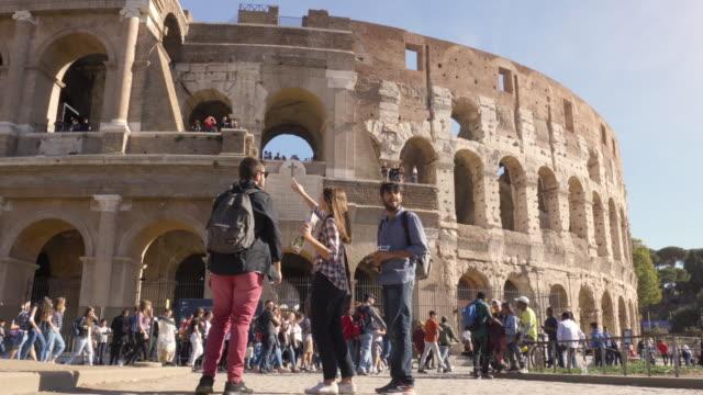 vidéos et rushes de trois jeunes amis touristes, debout devant le colisée de rome lecture carte guident pour obtenir des directives de pointage avec cheveux longs heureux belle fille lunettes de soleil de sacs à dos - rome