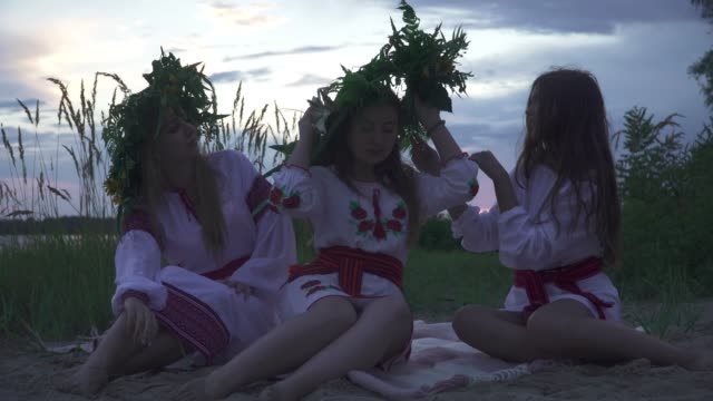 three young girls in national costumes on the beach - славянская культура стоковые видео и кадры b-roll