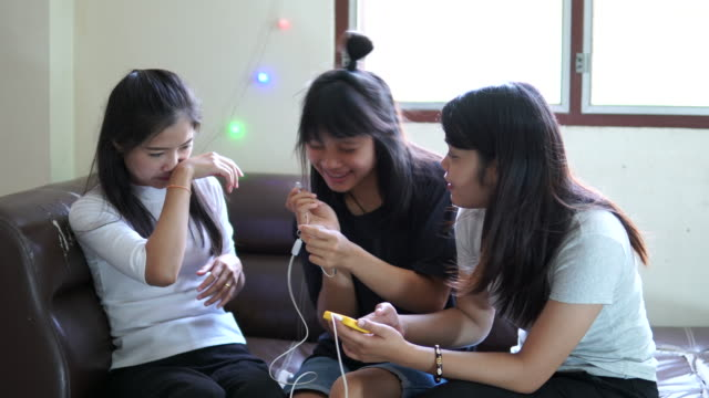 Three young happy girls are listening music from smartphone