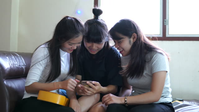 Three young happy girls are using a smartphone at home