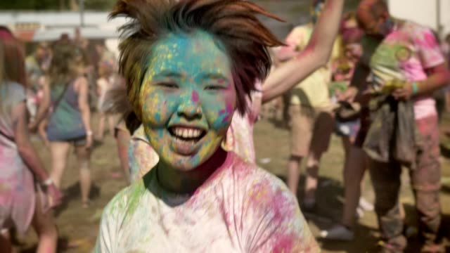 vídeos de stock e filmes b-roll de three young happy multi-ethnic girlfriends are jumping in conga line on holi festival in daytime in summer, friendship concept, holiday concept - holi