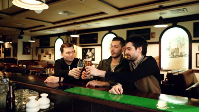 Tres hombres jóvenes en ropa casual están bebiendo cerveza en el bar de deportes Fantasia, címbalo vasos y botellas y hablando mientras está sentado en el mostrador. Chicos noche concepto. - vídeo