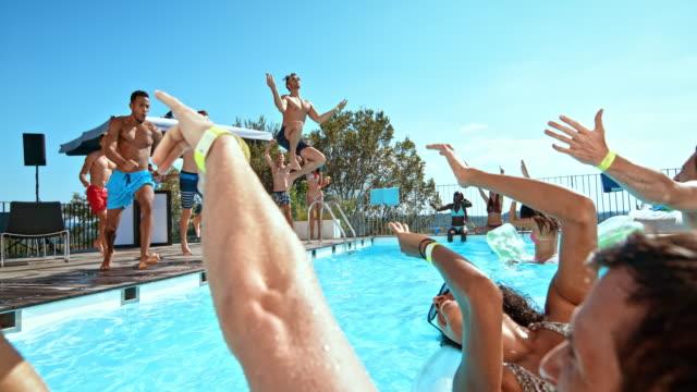 slo-mo-drei junge männer auf einer party in den pool springen und ihren freunden im wasser planschen - nackter oberkörper stock-videos und b-roll-filmmaterial