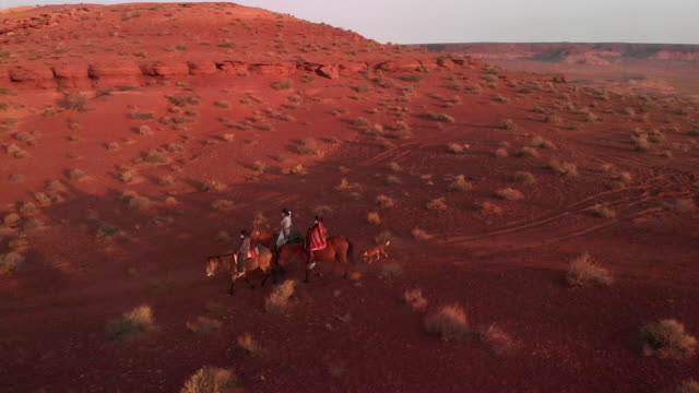 Three Young Teenage and Younger Siblings Navajo Native American People Riding their Horses Bareback in the Desert Near Monument Valley Tribal Park at Dusk in the Summer