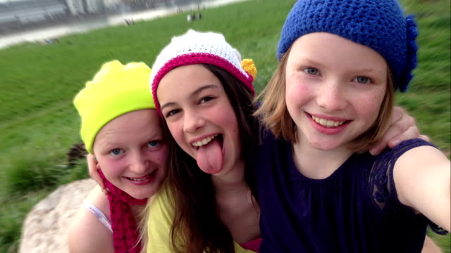 Three Young Teenage Girls taking Selfies, sticking out tongue, outdoors video