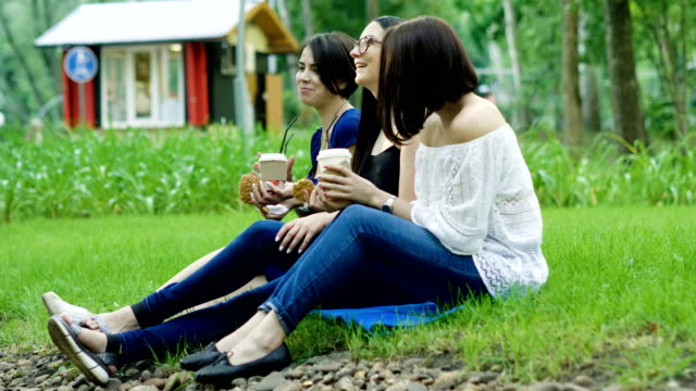 vídeos de stock e filmes b-roll de three young women drinking drinks and eating pastries in a summer park. 4k - só mulheres jovens
