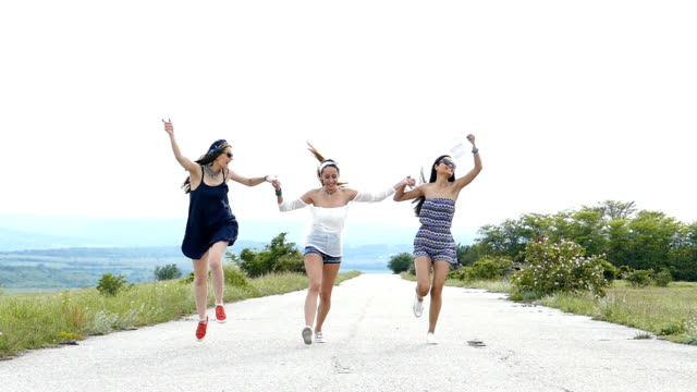 Three young women having fun on country road,slow motion video