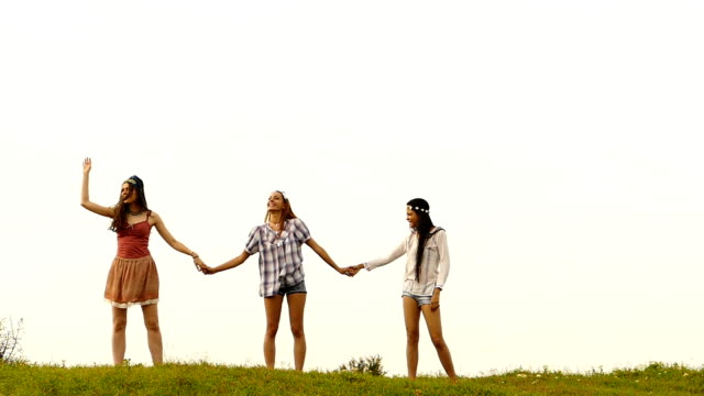 Three young women holding hands and singing,slow motion video