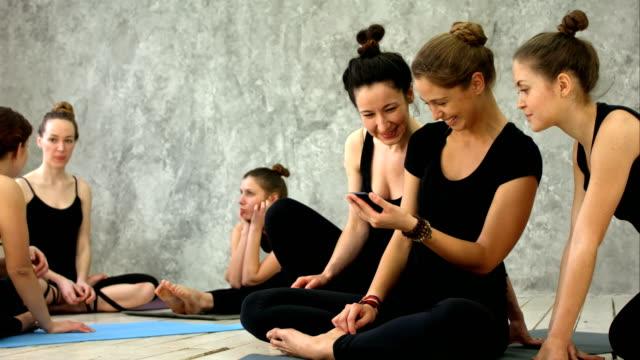 tre unga kvinnor avkopplande, använda smartphoe, talar efter träningspass på yogaklass - gym skratt bildbanksvideor och videomaterial från bakom kulisserna