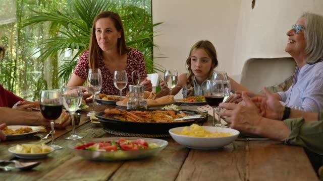 geleneksel öğle yemeğinin tadını çıkaran üç nesilaile - öğün stok videoları ve detay görüntü çekimi