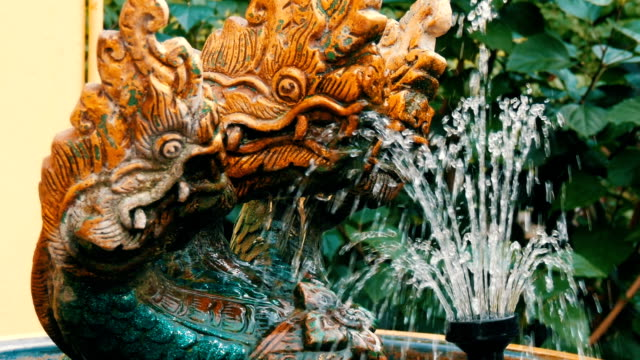 Three-headed green dragon as a traditional Buddhist symbol. Statue and a fountain of dragon in the garden of Thailand video