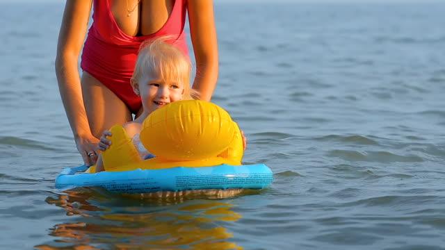 treårig flicka simmar i havet satt på gummiringen, simning och ler glatt. - inflatable ring bildbanksvideor och videomaterial från bakom kulisserna