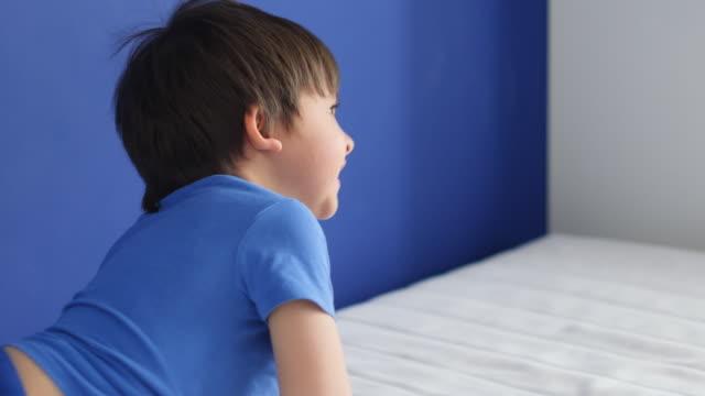 enfant de trois ans en pantalon bleu et un T-shirt saute sur un lit blanc - Vidéo