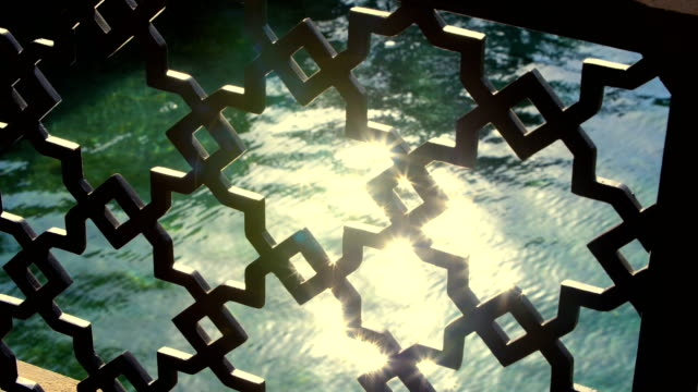 through a beautiful openwork lattice, you can see sunbeams on the water. close-up - paesi del golfo video stock e b–roll