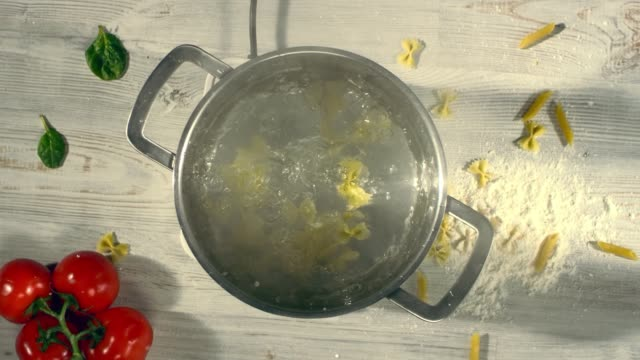 SLOW MOTION: throw a pasta in a steel pan. Top view. Shot with cinema camera RED DRAGON 240 fps