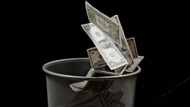 slo mo throwing american dollars bills into trash bin - потеря стоковые видео и кадры b-roll