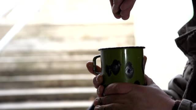 hd super slow-mo: throwing coins into cup of a homeless - dirty money bildbanksvideor och videomaterial från bakom kulisserna
