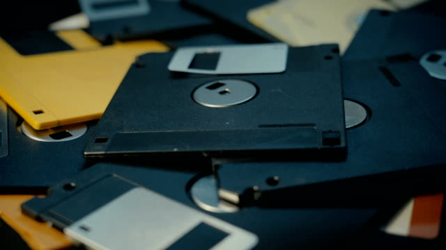 vídeos y material grabado en eventos de stock de lanzando discos de disquete en una pila, antigua tecnología retro - disquete