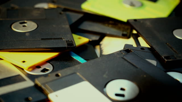Throwing floppy discs into a pile, old retro technology