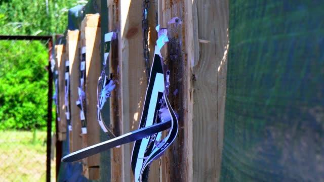 オープンエアの距離からターゲットで投げナイフ、投げナイフ、ナイフ、飛行のための競争シャープ木製スタンド、スローモーションからターゲットのナイフ フライ - 尖っている点の映像素材/bロール