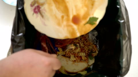 vídeos de stock e filmes b-roll de throwing leftovers to the trash can at home - food