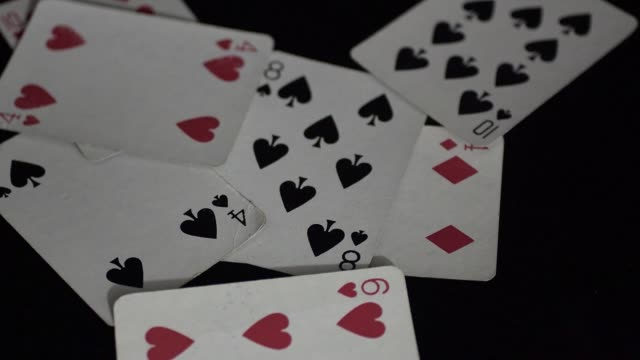 Throwing, or giving, playing cards on a black reflective surface