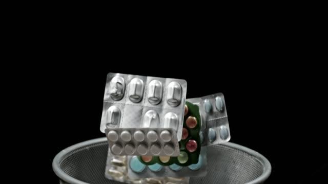 stockvideo's en b-roll-footage met slo mo gooien pillen in prullen mandje - doordrukstrip