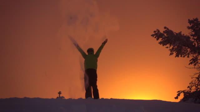 zeitlupe: werfen schnee bis in den himmel, arme stolz bei dem goldenen aufstieg - schneeflocke sonnenaufgang stock-videos und b-roll-filmmaterial