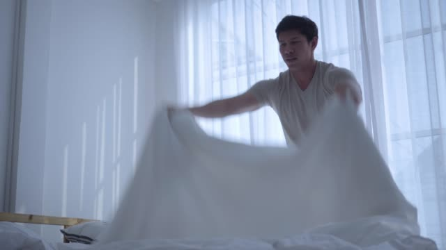 Throwing white blanket on bed