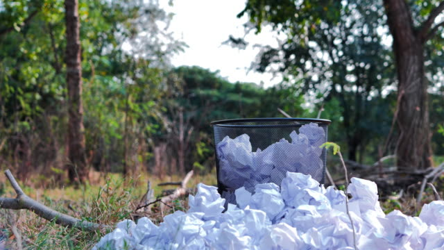 Thrown paper to metal basket bin in the jungle. recycle, Saving resources nature and environment concept. Slow Motion Thrown paper to metal basket bin in the jungle. recycle, Saving resources nature and environment concept. Slow Motion generation x stock videos & royalty-free footage