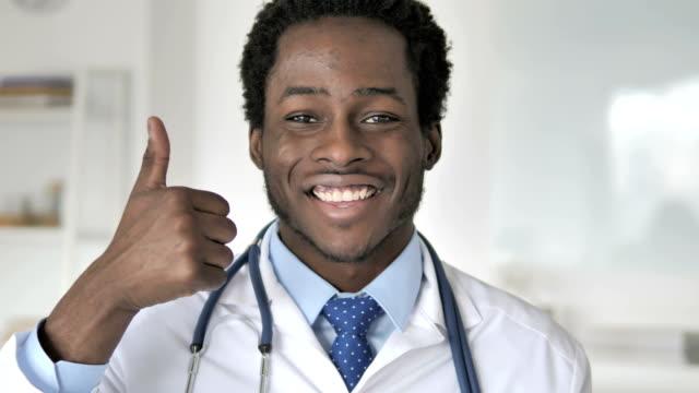 thumbs up by african doctor - znak ok filmów i materiałów b-roll