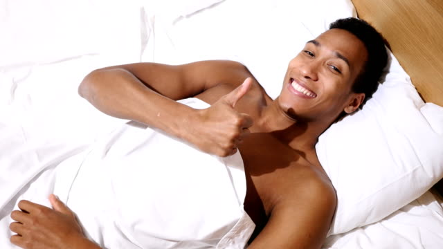 Thumbs Up by Happy African Man Lying in Bed, Top View video