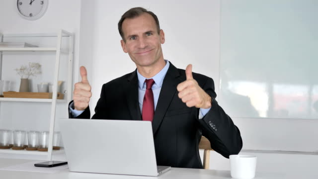 thumbs up by middle aged businessman looking at camera - thumbs up стоковые видео и кадры b-roll