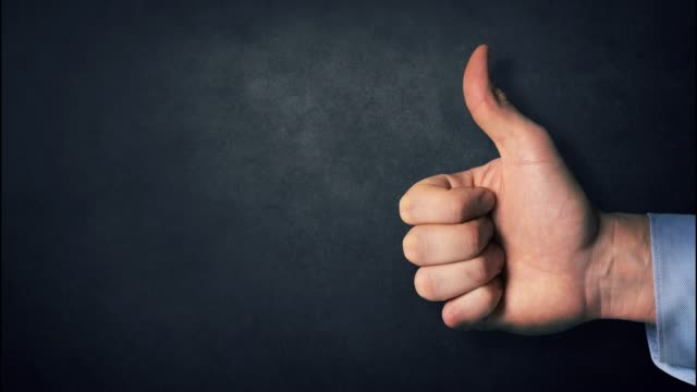 thumbs up - like or approve sign on dark black background with copy space