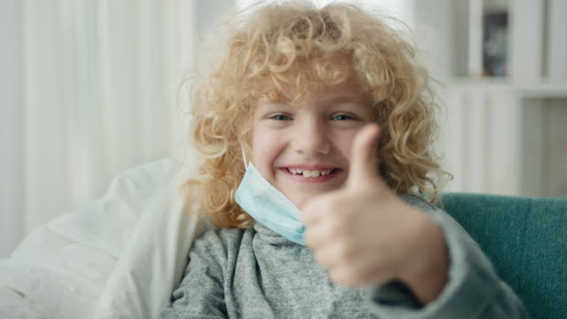 Thumbs up! Little boy showing thumbs up with face mask. covid icon stock videos & royalty-free footage