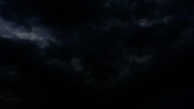 gewitterwolken in der nacht mit blitz. 4k zeitraffer schleife. - gewitter stock-videos und b-roll-filmmaterial