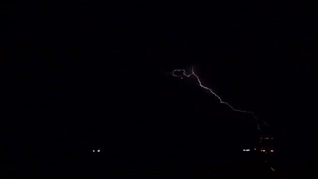 SLOW MOTION: Thunderstorm lightning bolt striking over highway traffic video