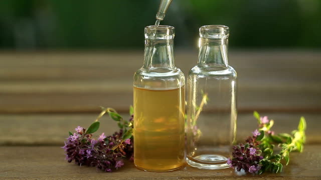 thyme essential oil in  beautiful bottle on table - oli, aromi e spezie video stock e b–roll