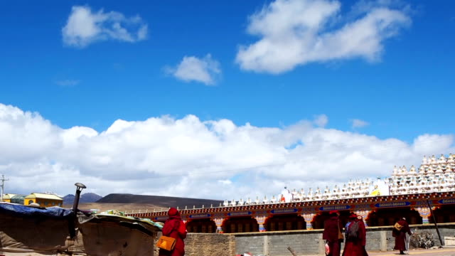 Tibetan buddhist monks and nuns walking at the pagodas in Yarchen Gar Monastery