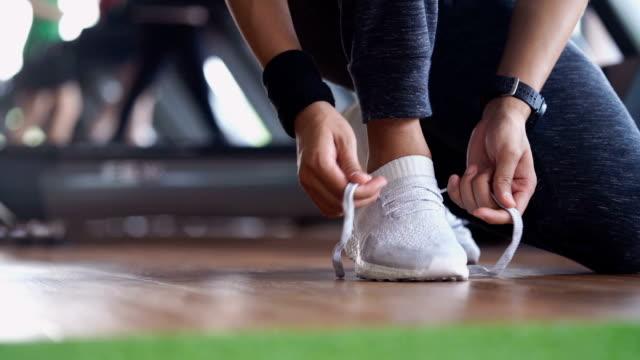 디딜 방 아 배경으로 체육관에서 화이트 스포츠 실행 실행 신발 넥타이 - 운동장비 스톡 비디오 및 b-롤 화면