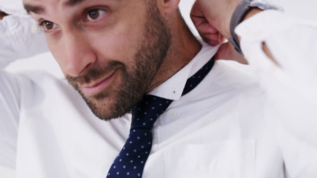 A tie will transform your look 4k vide footage of a man putting his tie on while standing against a white background button down shirt stock videos & royalty-free footage