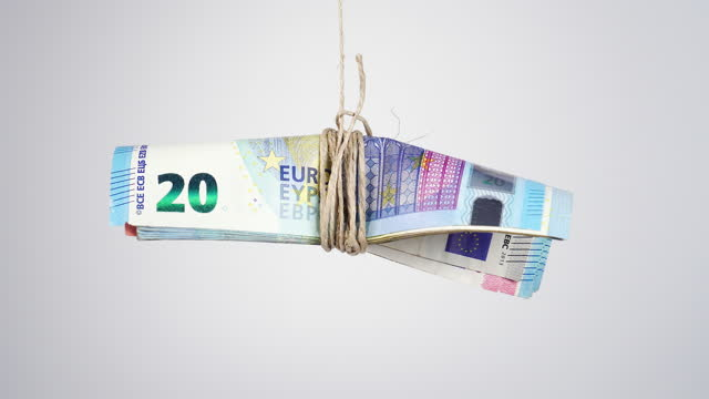 Tied euro banknotes hang on a rope