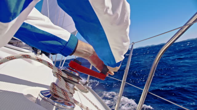 SLO MO Tightening the rope on a sailboat Slow motion shot of man tightening a rope around a winch on a sailboat sailing on the sea.  Adriatic Sea. Croatia. regatta stock videos & royalty-free footage