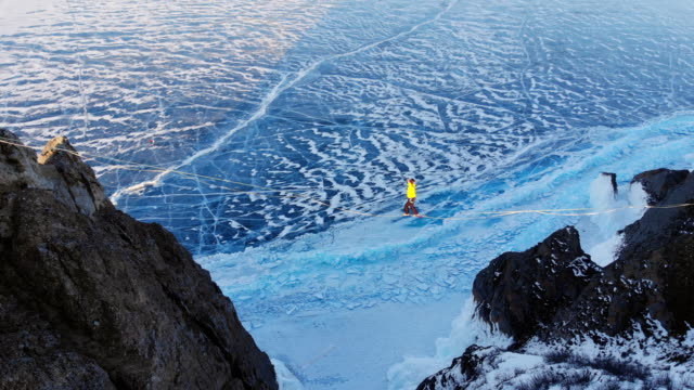 Tightrope Walker on the background of blue ice frozen lake.