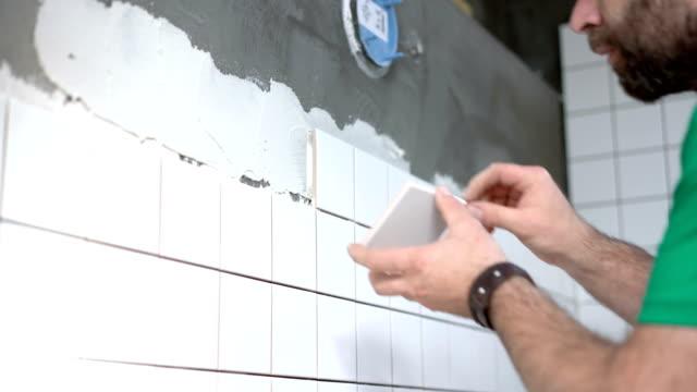 Tile mason installing ceramic tiles