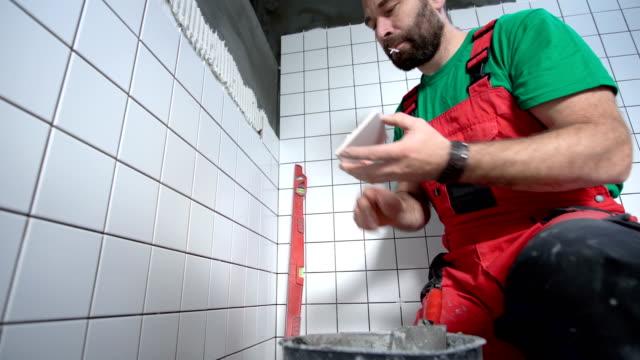 Tile mason laying tiles in the bathroom