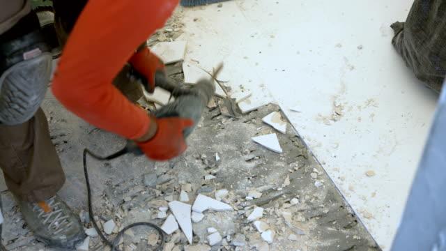 kakel mason att ta bort gamla plattor från badrumsgolvet - construction workwear floor bildbanksvideor och videomaterial från bakom kulisserna