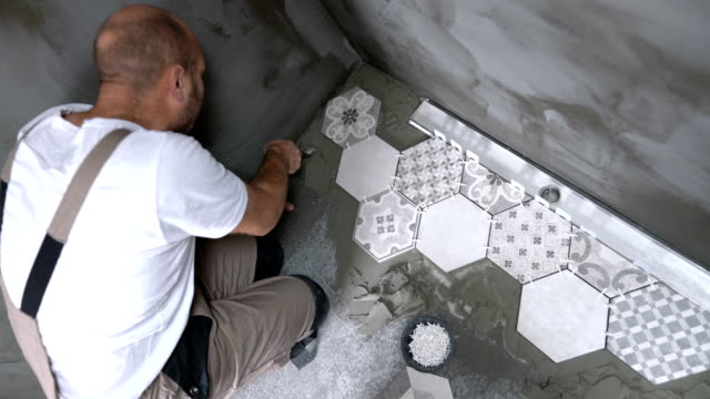 kakel mason sprider kakel lim på bad rums golvet - construction workwear floor bildbanksvideor och videomaterial från bakom kulisserna